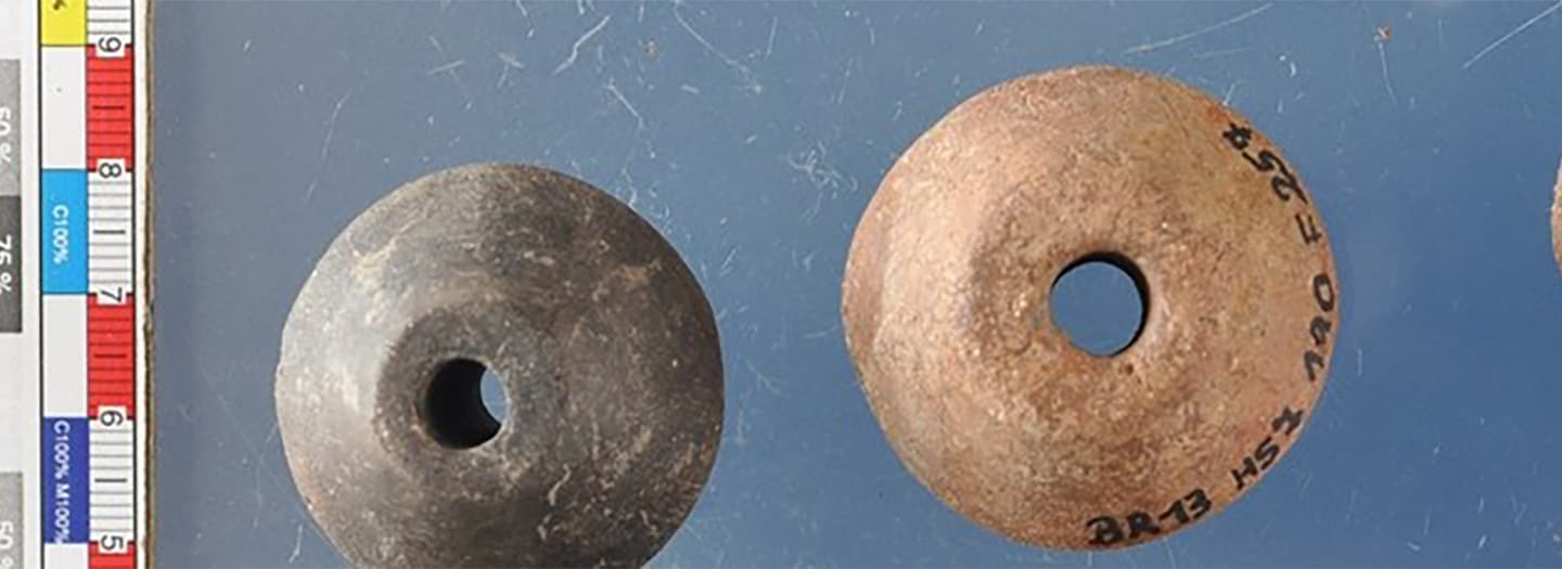 "alt=""Two ceramic spindle whorls with a scale"""
