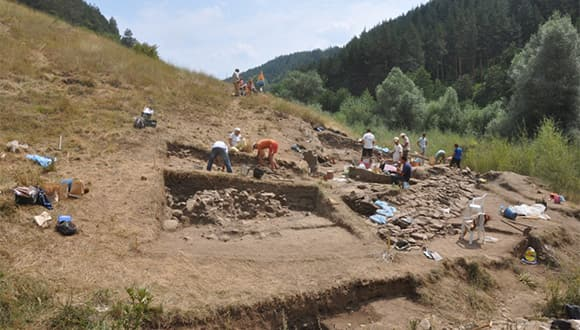 Students excavating on a hillside