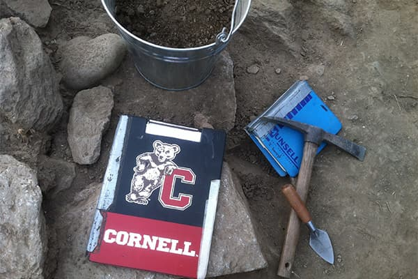 Cornell notebook sitting on an ancient wall with bucket, trowel, and pickax