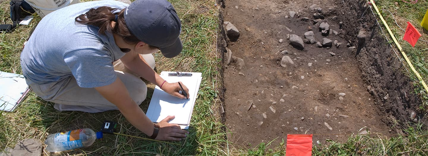Archaeologist writing notes near excavation unit