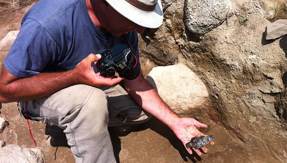 Archaeologist holding camera and projectile point