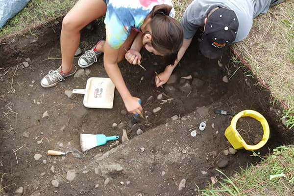 Archaeologists digging with brush and dustpan